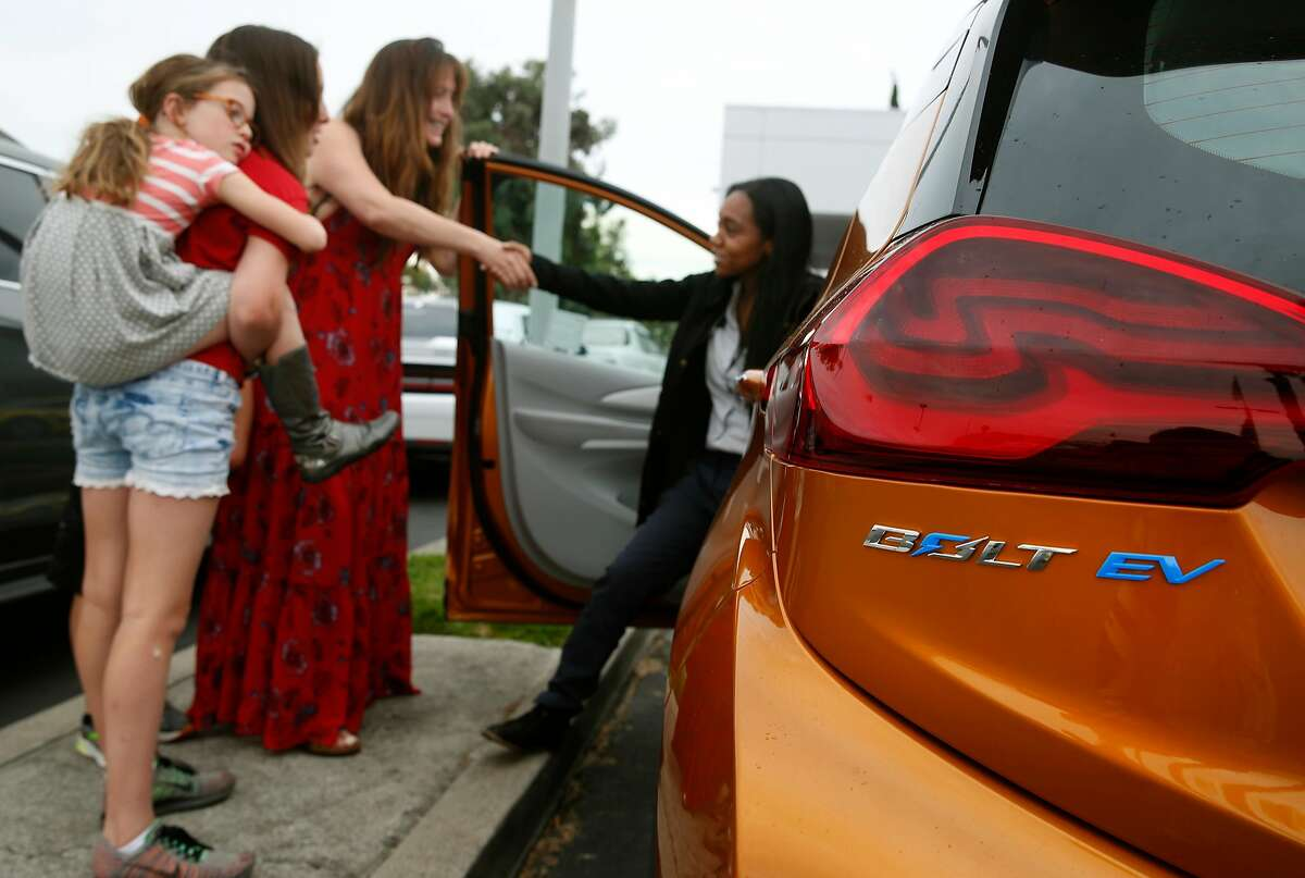Sales associate Devani Knox (right) thanks Dana Nachman and her daughters Sidney, 7, Annie, 11, and son Charlie, 10, for test driving a Bolt EV all-electric car at a Chevrolet dealership in Fremont, Calif. on Friday, Aug. 4, 2017. Proposed state legislation may provide instant rebates to boost sales of plug-in vehicles.