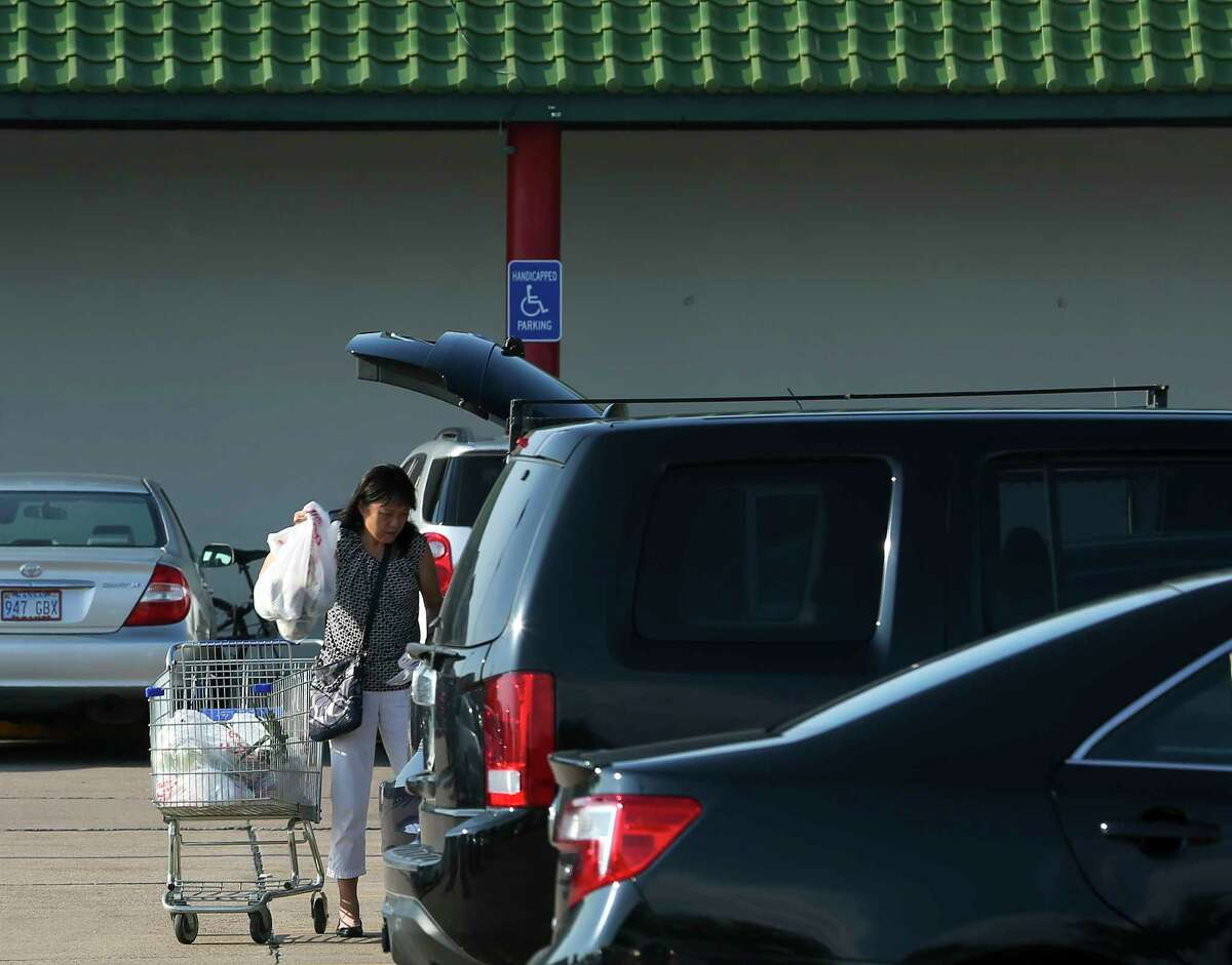 A shopper loads her groceries into the trunk of her car after shopping at Jusgo Supermarket Friday, Aug. 4, 2017, in Houston. Shoppers avoid shopping in Chinatown during the night hours to protect against an uptick in daylight robberies against Asians in the parking lots.Harris County District Attorney Kim Ogg and top Houston Police Department brass will attend a community meeting in Chinatown to address a rash of robberies that didn't subside after a community effort last summer.