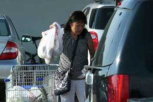 A shopper loads her grocery into the trunk of his car after shopping at Jusgo Supermarket Friday, Aug. 4, 2017, in Houston. Shoppers avoid shopping at Jusgo Supermarket and Welcome Food Center during the night to defend themselves against an uptick in daylight robberies at the parking lots. Harris County District Attorney Kim Ogg and top Houston Police Department brass will attend a community meeting in Chinatown to address a rash of robberies that didn't subside after a community effort last summer.