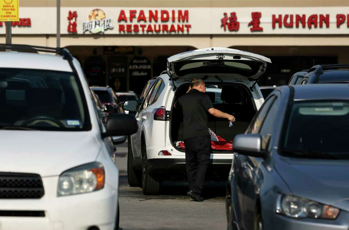 A shopper loads his groceries into the trunk of his car after shopping at a supermarket Friday, Aug. 4, 2017, in Houston. Shoppers avoid shopping in Chinatown during the night hours to protect against an uptick in daylight robberies against Asians in the parking lots. Harris County District Attorney Kim Ogg and top Houston Police Department brass will attend a community meeting in Chinatown to address a rash of robberies that didn't subside after a community effort last summer.