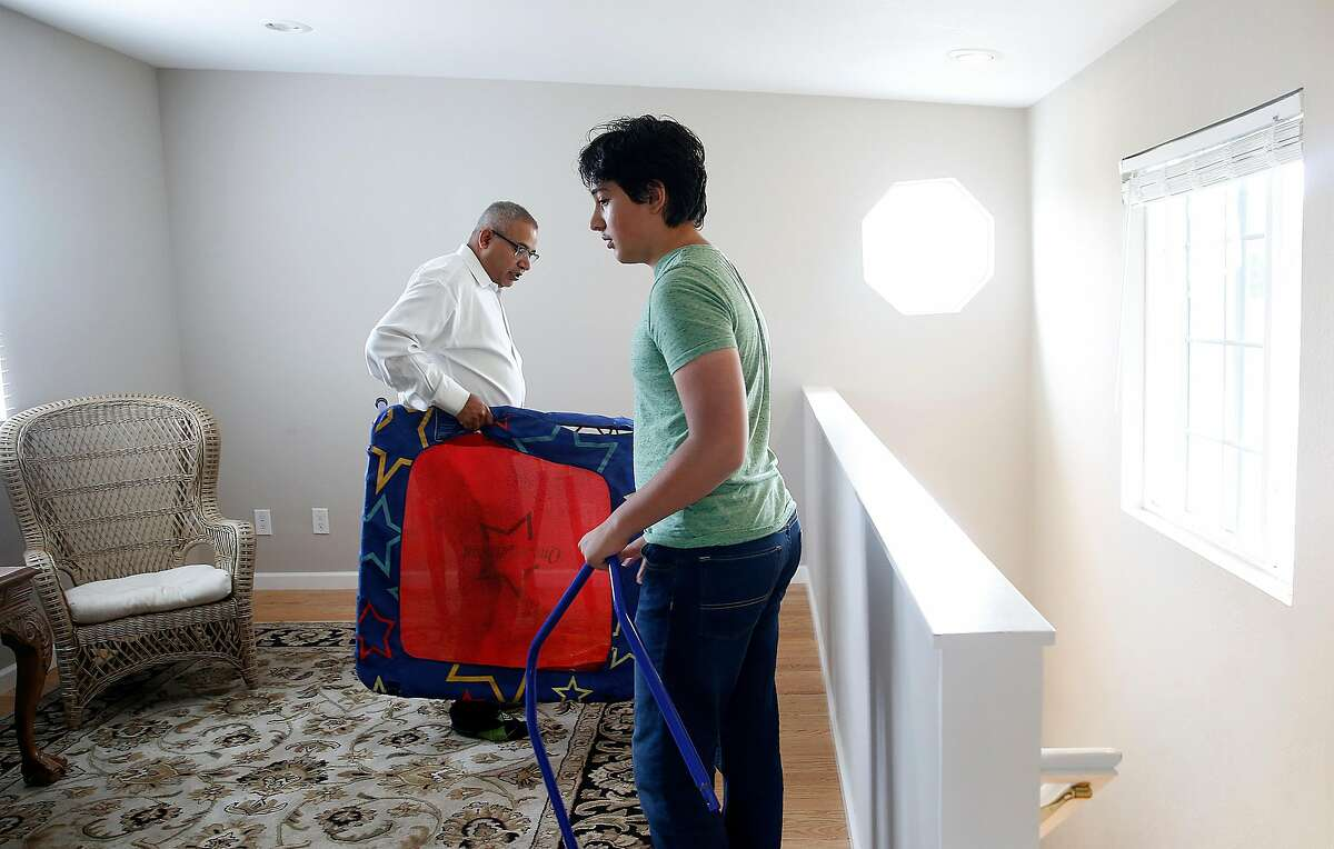 Srinidhi Thirumala (back left) with his son Ayush Thirumala (right) as they place items in their new home on Friday, August 3, 2017, in Mountain View, Calif.