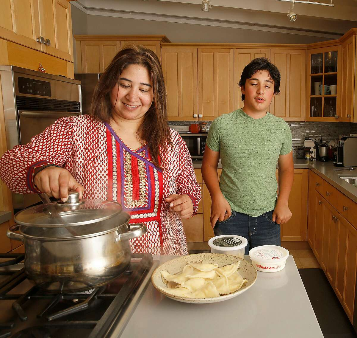 Sowmya Rangaswamy (left) makes lunch with her son Ayush Thirumala (right), 13, in their new home on Friday, August 3, 2017, in Mountain View, Calif.