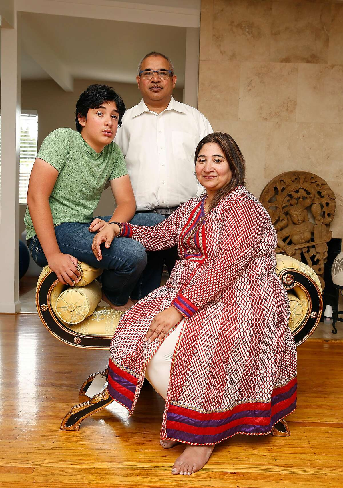 Ayush Thirumala (left), 13, with his dad Srinidhi Thirumala (white shirt), and mom Sowmya Rangaswamy (front) in their new home on Friday, August 3, 2017, in Mountain View, Calif.