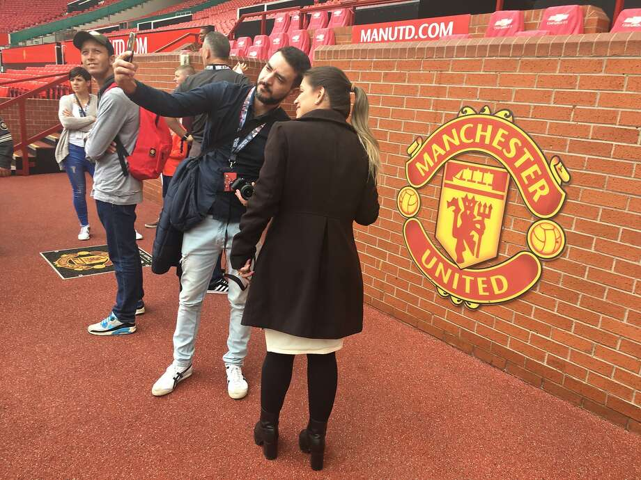 Manchester United fans from around the world take advantage of photo ops during a stadium tour. Photo: Jeanne Cooper, Special To The Chronicle