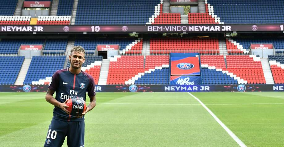"""TOPSHOT - Brazilian superstar Neymar poses with a ball during his official presentation at the Parc des Princes stadium on August 4, 2017 in Paris after agreeing a five-year contract following his world record 222 million euro ($260 million) transfer from Barcelona to Paris Saint Germain's (PSG). Paris Saint-Germain have signed Brazilian forward Neymar from Barcelona for a world-record transfer fee of 222 million euros (around $264 million), more than doubling the previous record. Neymar said he came to Paris Saint-Germain for a """"bigger challenge"""" in his first public comments since arriving in the French capital. / AFP PHOTO / PHILIPPE LOPEZPHILIPPE LOPEZ/AFP/Getty Images Photo: PHILIPPE LOPEZ/AFP/Getty Images"""