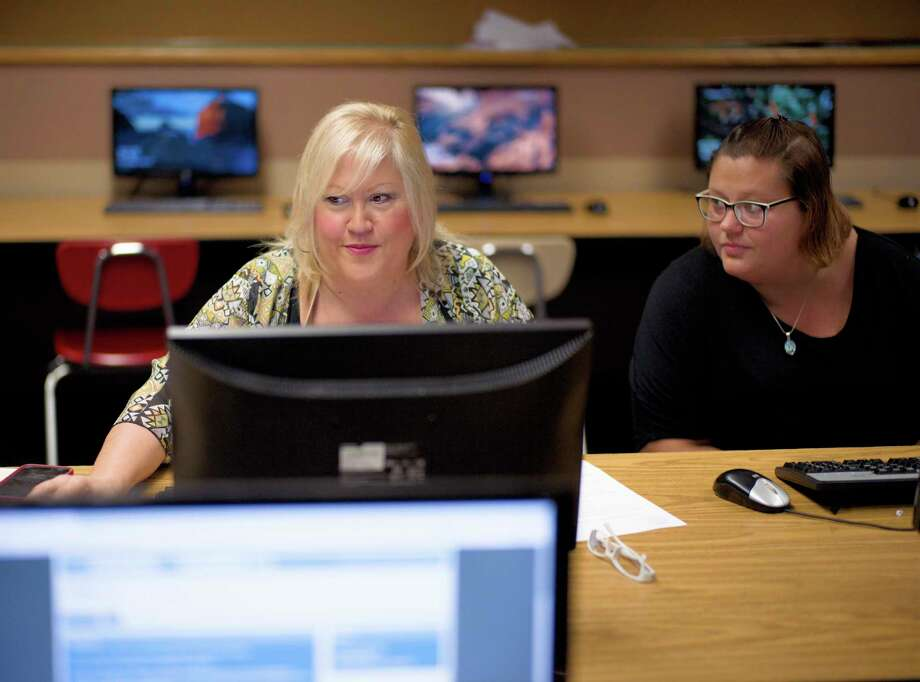 In this Thursday, July 27, 2017, photo, Cheryl Bast, left, is accompanied by her daughter Liz Pierson, as she works on an application for a position with Omaha Public Schools, during a job fair held at Omaha South High School in Omaha, Neb. On Friday, Aug. 4, 2017, the U.S. government issues the July jobs report. (AP Photo/Nati Harnik) Photo: Nati Harnik, STF / Copyright 2017 The Associated Press. All rights reserved.