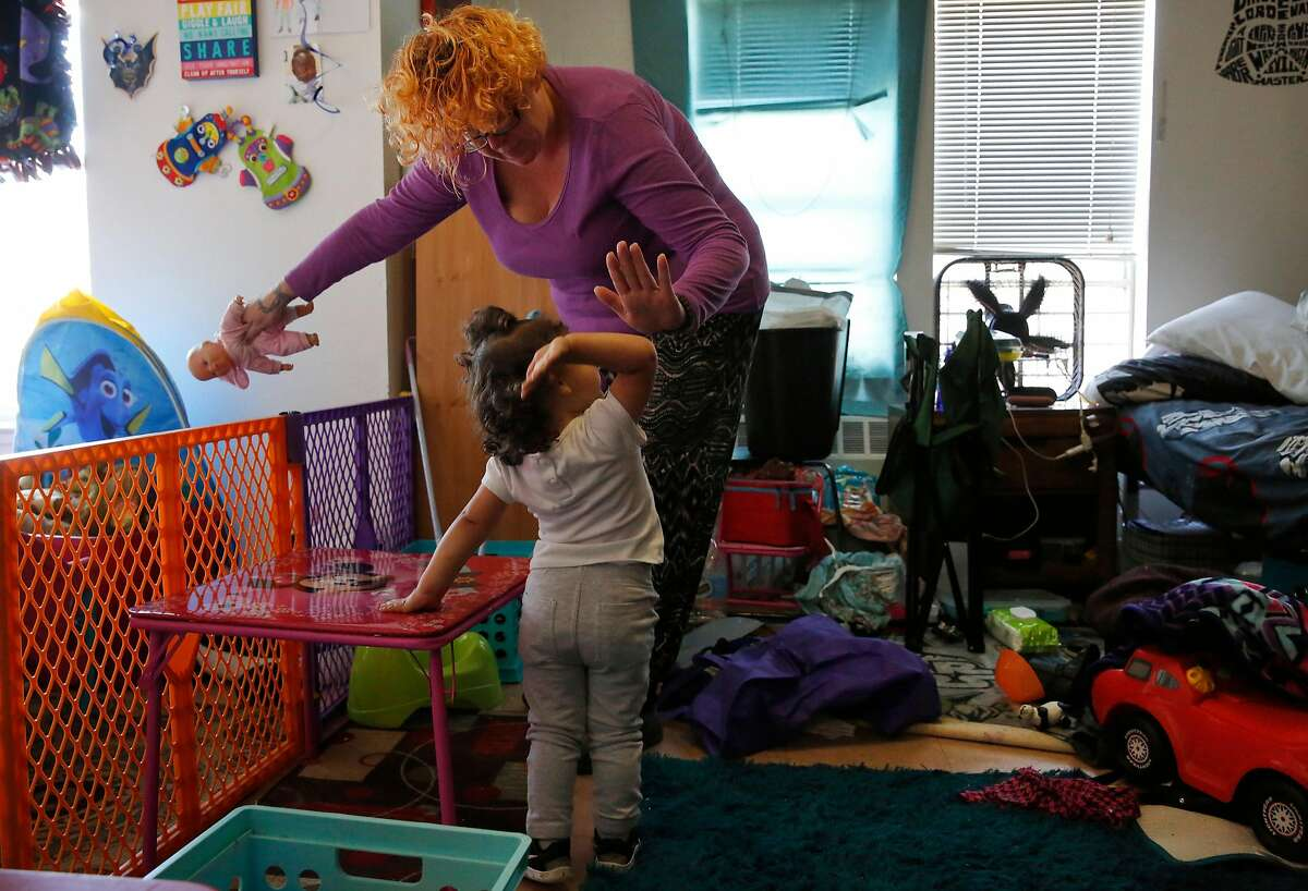 """Jennifer Shoop high fives her daughter Madrox, 2, as she cleans up in their room at Hamilton Families transitional housing August 2, 2017 in San Francisco, Calif. Shoop was previously homeless and addicted to drugs. She had quit the """"hard stuff"""" and she says she was on her way to relapse when she found out she was pregnant with twins and chose to stay clean and start to turn her life around."""