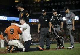 San Francisco Giants' Brandon Belt (9) is tended to by manager Bruce Bochy, top left, and trainer Dave Groeschner after being hit by a pitch by Arizona Diamondbacks pitcher Anthony Banda (50) during the sixth inning of a baseball game in San Francisco, Friday, Aug. 4, 2017. Also pictured are umpire Scott Barry, center, and catcher Chris Iannetta, second from right. (AP Photo/Jeff Chiu)
