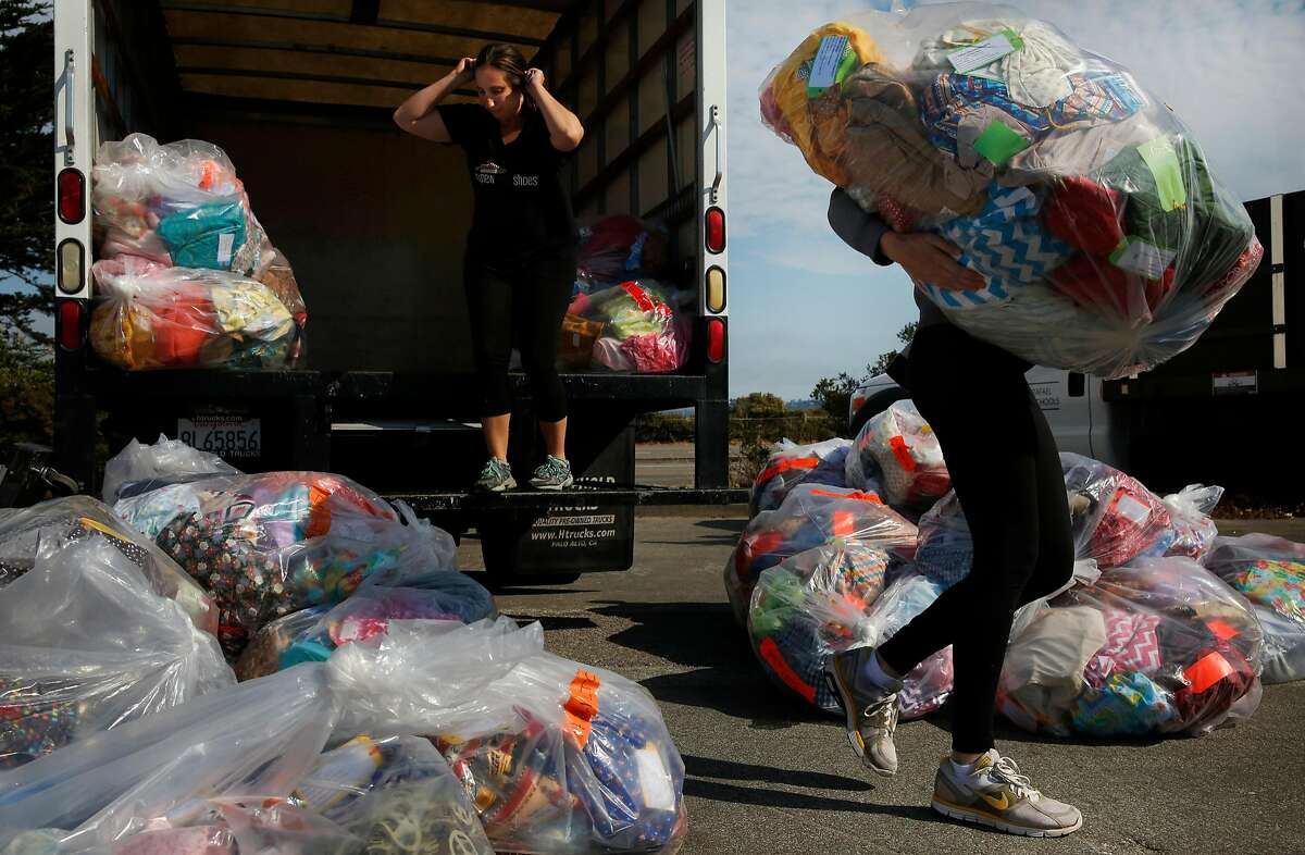 Julia Neff, right, of San Rafael City Schools takes a sack full of donated items from Becca Winslow with My New Red Shoes outside of the Sports Basement in the presidio August 2, 2017 in San Francisco, Calif. My New Red Shoes donated custom back-to-school packages to Hamilton Families and others to be given out to families right before the start of the school year.