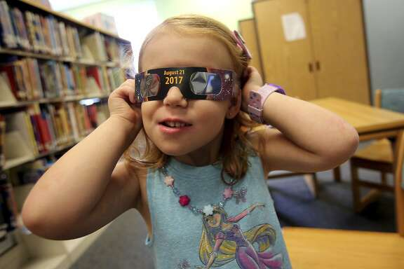 Emmalyn Johnson, 3, tries on her free pair of eclipse glasses at Mauney Memorial Library in Kings Mountain, N.C., Wednesday, Aug. 2, 2017. Glasses are being given away at the library for free while supplies last ahead of the big event on August 21. (Brittany Randolph/The Star via AP)