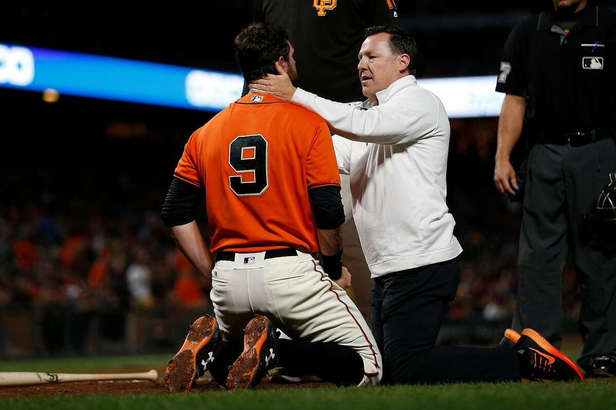Head trainer Dave Groeschner looks at the Giants' Brandon Belt after the first baseman was hit by a pitch on Aug. 4.