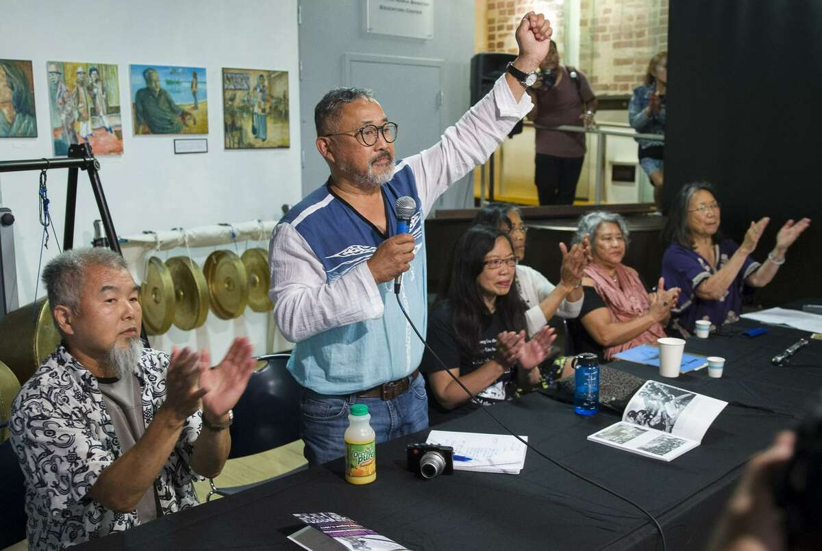 """Emil De Guzman, who was president of the International Hotel Tenants Association at the time of the evictions, makes a fist in a show of solidarity during the """"Original Defenders"""" panel."""