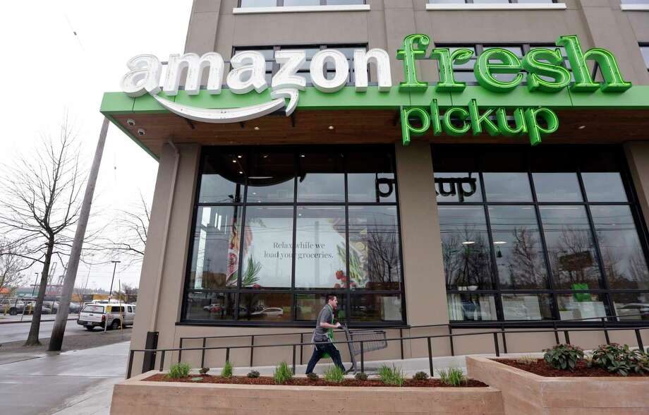 FILE - In this Tuesday, March 28, 2017, file photo, an Amazon worker wheels back a cart after loading a bag of groceries into a customer's car at an AmazonFresh Pickup location in Seattle. Amazon.com Inc. reports financial earnings Thursday, April 27, 2017. (AP Photo/Elaine Thompson, File) Photo: Elaine Thompson, STF / Copyright 2017 The Associated Press. All rights reserved.