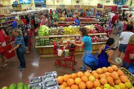 Customers shop at Trader Joe's in The Woodlands. According to a new study, having a Trader Joe's in the neighborhood is good for home values.
