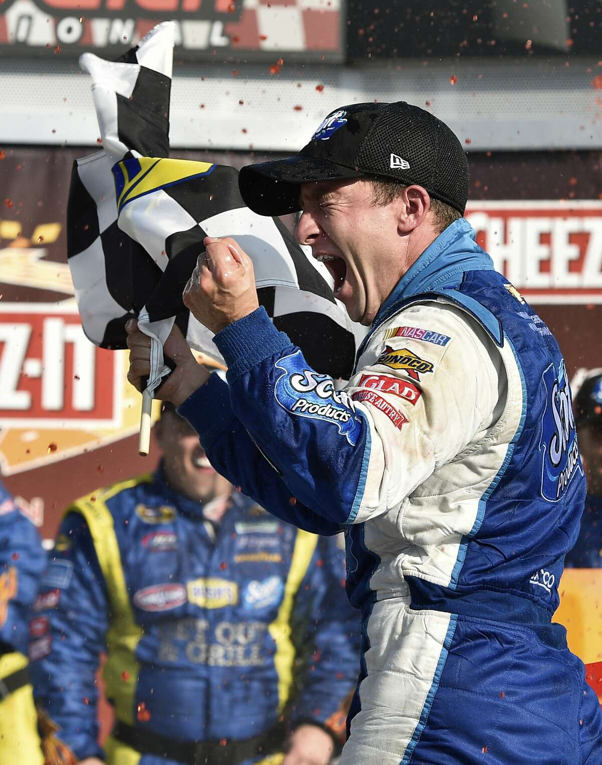 FILE- In this Aug. 10, 2014, file photo, AJ Allmendinger waves the checkered flag as he celebrates in Victory Lane after winning a NASCAR Sprint Cup series auto race at Watkins Glen International in Watkins Glen, N.Y. Allmendinger returns to Watkins Glen on Sunday, Aug. 6, where he can use a win to qualify for NASCAR's postseason. (AP Photo/Derik Hamilton, File)
