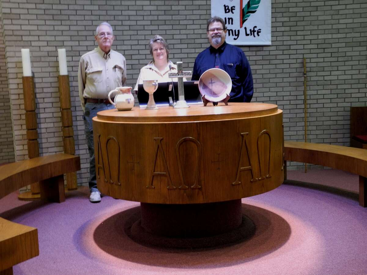 Longtime First Presbyterian member Dr. Richard Morton stands with Karen Hawkins and Pastor David Hawkins behind the communion table of First Presbyterian Church.