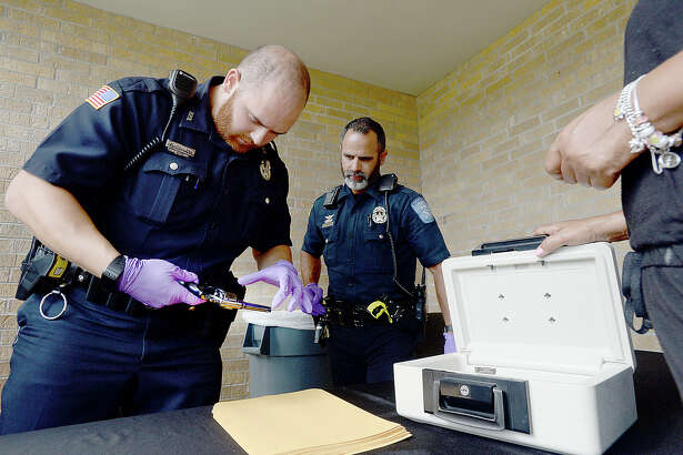 Beaumont police officers McCauley (left) and Proenza work the gun collection table, checking weapons before sealing them in manila envelopes and loading them into a police vehicle during the gun buyback program held Friday at Cathedral Church. The church was one of five locations throughout Beaumont that took part in the event. Citizens could remain anonymous and received vouchers which were turned in immediately for cash in amounts ranging from $100 to $300 depending on the gun type. The event was organized to help get illegal firearms off the streets and out of the hands of criminals. It comes in the wake of a series of shootings throughout the summer, the most recent resulting in the death of a man in the Beaumont's north end Wednesday. $31,000 was raised for the program through a community-wide effort that included businesses, law enforcement, churches, individuals, and community organizations such as the Not in My City movement.  Photo taken Friday, August 4, 2017 Kim Brent/The Enterprise