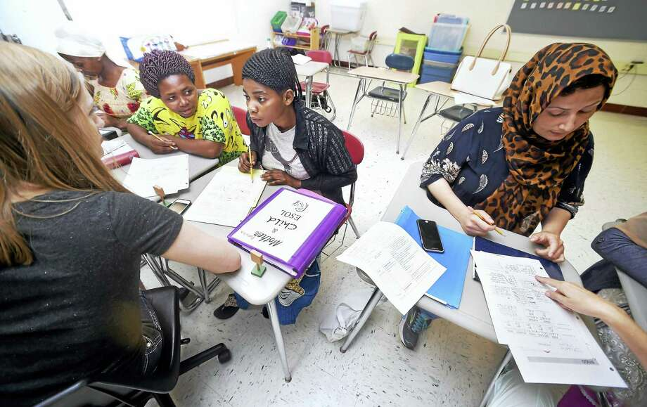 Left to right, volunteer Allison Reinhardt assists Nyasa and Furaha of the Democratic Republic of the Congo during an English class at Wilbur Cross High School in New Haven as Laili of Afghanistan works with another volunteer. Photo: Arnold Gold / Hearst Connecticut Media / New Haven Register