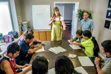 The Rev. Debbie Buchholz, center, leads an American Sign Language class for deaf refugees in Kansas City, Kan. Near Buchholz is volunteer tutor John Kingsley, right. Buchholz, who is hard of hearing herself, runs a program for deaf refugees through her Olathe church. (Allison Long/Kansas City Star/TNS)