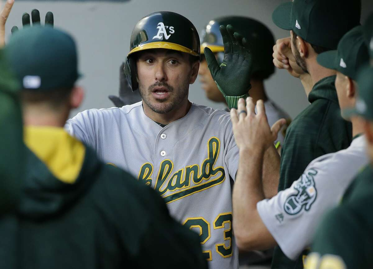 Oakland Athletics' Matt Joyce is greeted in the dugout after he scored on a double by Marcus Semien during the third inning of the team's baseball game against the Seattle Mariners, Friday, July 7, 2017, in Seattle.