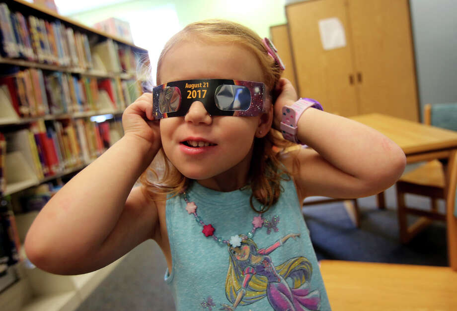 FILE - In this Wednesday, Aug. 2, 2017 file photo, Emmalyn Johnson, 3, tries on her free pair of eclipse glasses at Mauney Memorial Library in Kings Mountain, N.C. Glasses are being given away at the library for free while supplies last ahead of the big event on Aug. 21. (Brittany Randolph/The Star via AP) Photo: Brittany Randolph, MBI / Copyright 2017 The Associated Press. All rights reserved.