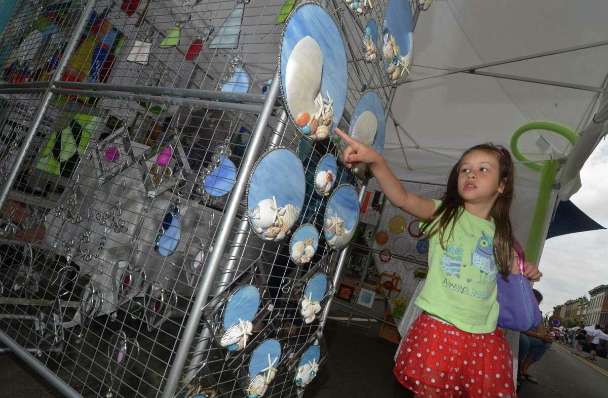 Cattleya Londono, 5, looks at the seashell ornaments at the SoNo Arts Festival on Saturday on the streets of historic South Norwalk .