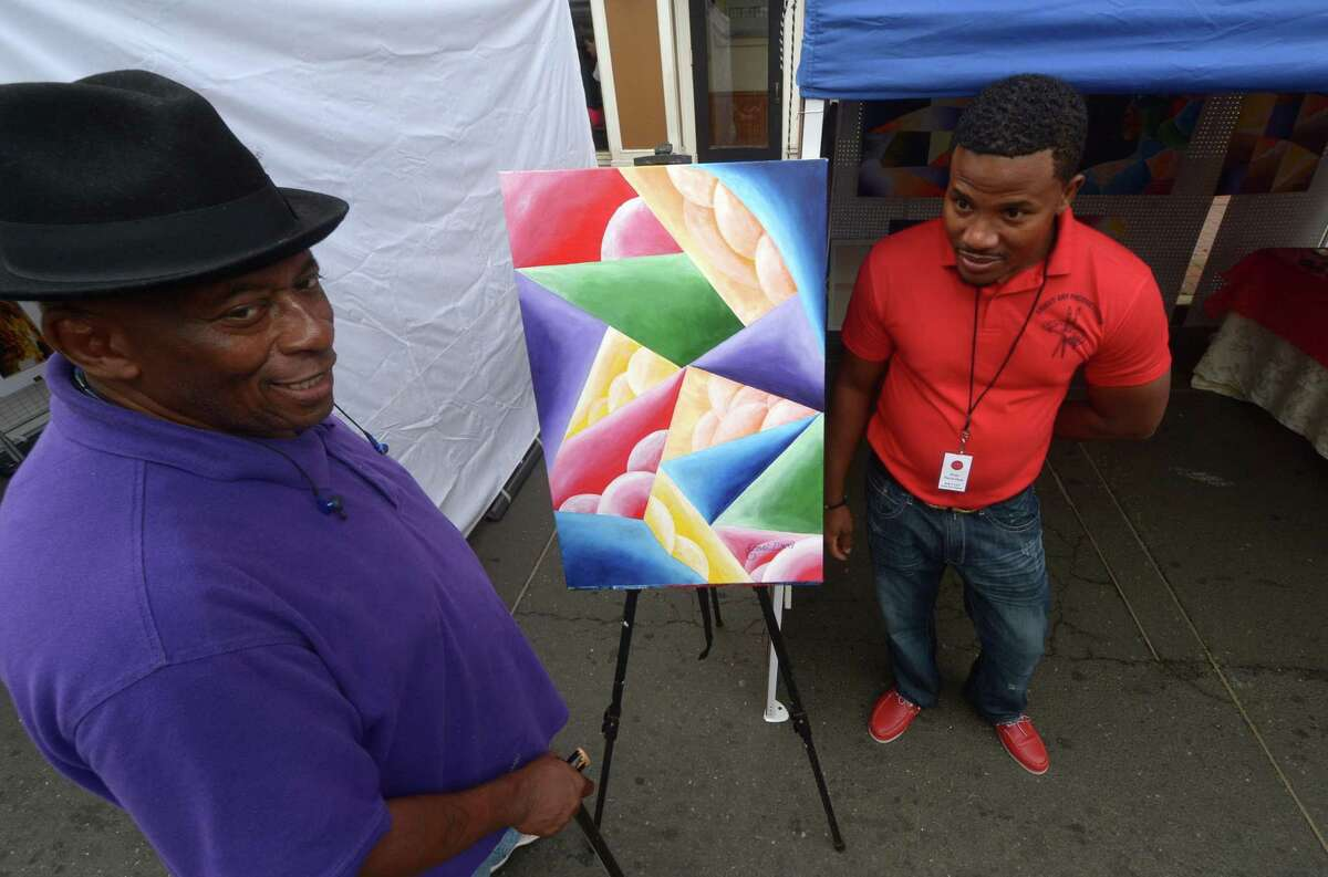 James Bullock checks out the paintings by Ernst Pierre-Noel at The SoNo Arts Festival Saturday, August 5, 2017, on the streets of historic South Norwalk, Conn. The SoNo Arts Festival showcases the works of over 100 juried artists with live bands, tempting food vendors, special discounts at SoNo shops and restaurants. The festival continues Sunday with a puppet parade at 2pm.
