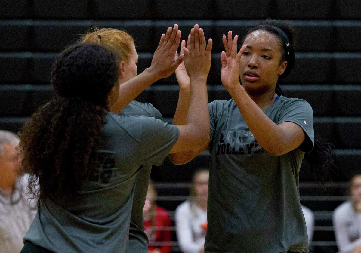 Victoria Ratcliff of Conroe gives a high-five from Jazzmin Kim during a high school volleyball scrimmage at Porter High School, Friday, Aug. 4, 2017, in Porter.