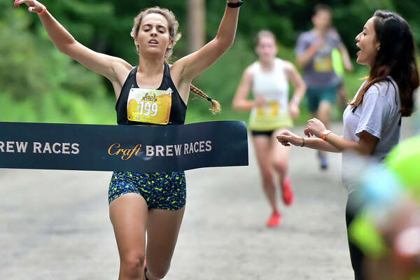 (Peter Hvizdak / Hearst Connecticut Media) New Haven, Connecticut: August 5, 2017. Jennifer Fannon of Bristol is the first female runner to cross the finish line during  the Craft Brew Race 5K run Saturday in New Haven at Edgewood Park. The race is followed by a beer festival featuring both local and regional breweries. A portion of each ticket sold for the race is donated to The Westville Village Renaissance Alliance.