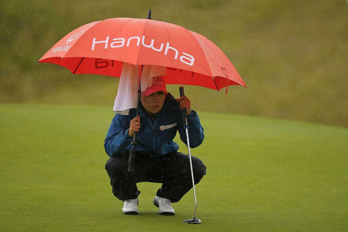 Korea's In-Kyung Kim reacts shelters under an umbrella as she lines up her putt on the 18th green during her second round on day 2 of the 2017 Women's British Open Golf Championship at Kingsbarns Golf Links near St. Andrews, east Scotland, on August 4, 2017. / AFP PHOTO / Andy BUCHANANANDY BUCHANAN/AFP/Getty Images