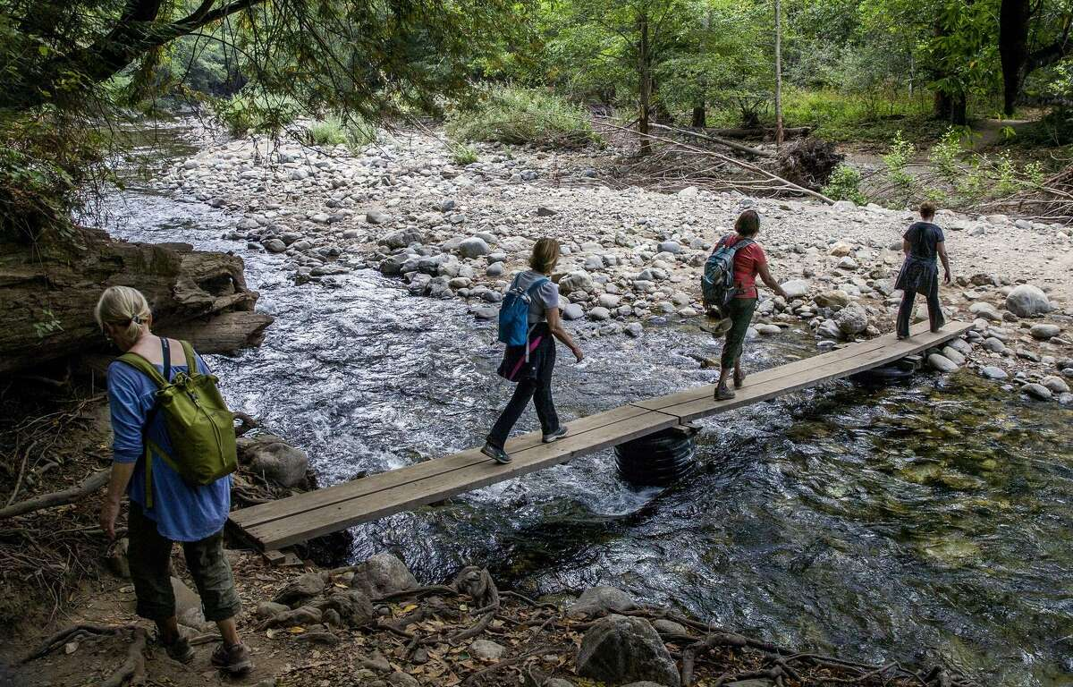 Hikers cross a footbridge on the Big Sur bypass trail that allows access to the area cut off by the Pfeiffer Canyon Bridge closure.