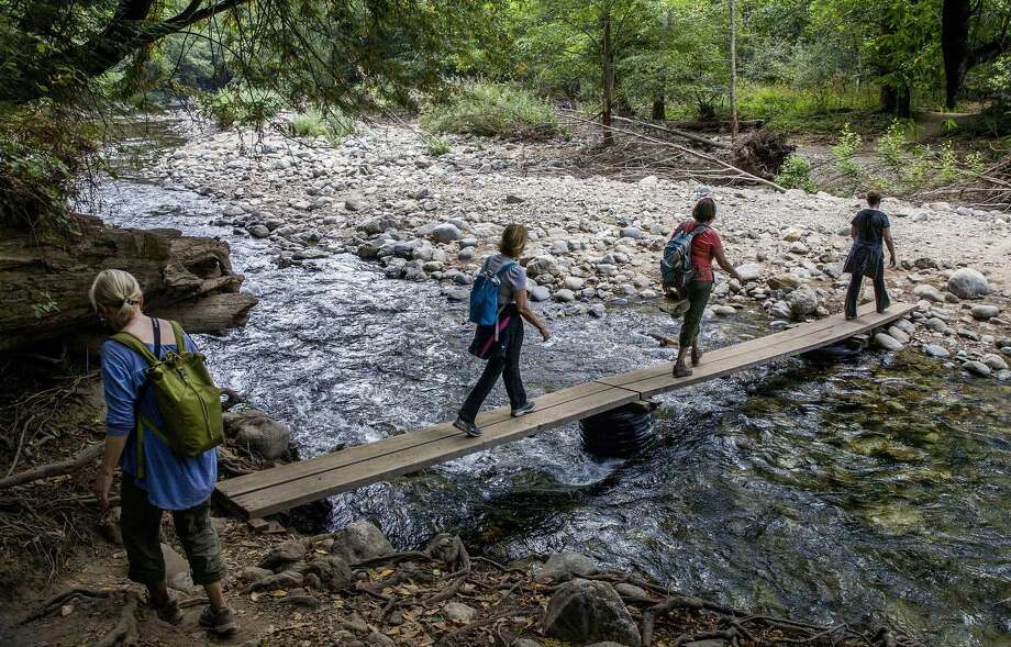 Hikers cross a footbridge on the Big Sur bypass trail that allows access to the area cut off by the Pfeiffer Canyon Bridge closure. Photo: Santiago Mejia / Photos By Santiago Mejia / The Chronicle / ONLINE_YES
