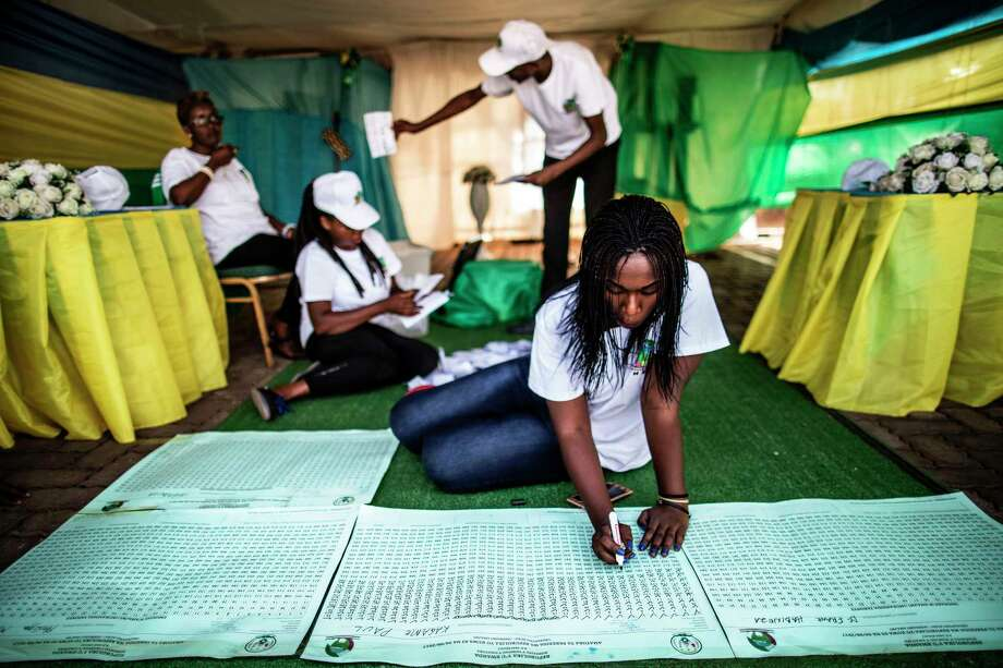Rwandan election officials use a counting board at a polling station Friday. Incumbent Paul Kagame earned over 98 percent of the votes cast for president. Photo: MARCO LONGARI, Contributor / AFP or licensors