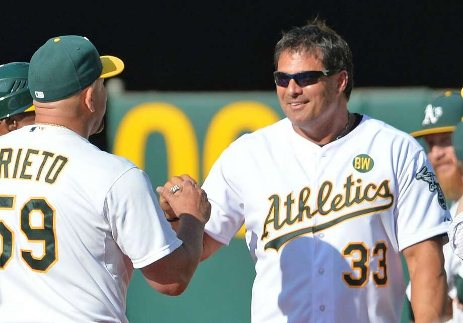 FILE-- Oakland Athletics coach Ariel Prieto, left, congratulates former A's player Jose Canseco during a pregame celebration honoring the 1989 World Series championship team before the start of play against the Baltimore Orioles at O.Co Coliseum in Oakland on Saturday, July 19, 2014. Tuesday, NBC Sports California severed ties with Canseco after he posted an incendiary string of tweets referencing sexual harassment. Photo: Doug Duran, TNS