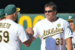 Oakland Athletics coach Ariel Prieto, left, congratulates former A's player Jose Canseco during a pregame celebration honoring the 1989 World Series championship team before the start of play against the Baltimore Orioles at O.Co Coliseum in Oakland, Calif., on Saturday, July 19, 2014. (Doug Duran/Bay Area News Group/MCT)