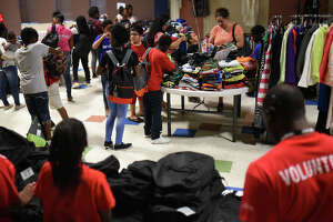 """Families gather clothes and school items during a free event called """"Community Fest"""" hosted by Community Worship Center on Aug. 5, 2017, at the Martin Luther King Center. The event supplies families with school uniforms and other clothes for free. James Durbin/Reporter-Telegram"""