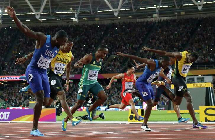 Justin Gatlin, left, of the United States, crosses the finish line to win gold in the men's 100 meters ahead of silver medalist and countryman Christian Coleman, second from the right. Jamaica's Usain Bolt, right, finished third. It marked the first bronze medal in a world championships for Bolt, who is accustomed to winning gold medals in the 100.