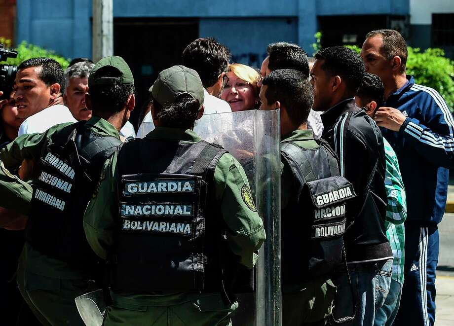 TOPSHOT - Venezuela's chief prosecutor Luisa Ortega (C), one of President Nicolas Maduro's most vocal critics, is surrounded by people and national guards during a flash visit to the Public Prosecutor's office in Caracas on August 5, 2017 as national guard units are posted at the entries and exits to the building. Venezuela's contested new assembly fired the country's dissident attorney general Ortega on Saturday in a move sure to provoke greater international criticism. The body, which made the sacking its first order of business, also said it planned to operate as Venezuela's supreme power for up to two years.  / AFP PHOTO / Ronaldo SCHEMIDTRONALDO SCHEMIDT/AFP/Getty Images Photo: RONALDO SCHEMIDT / AFP or licensors