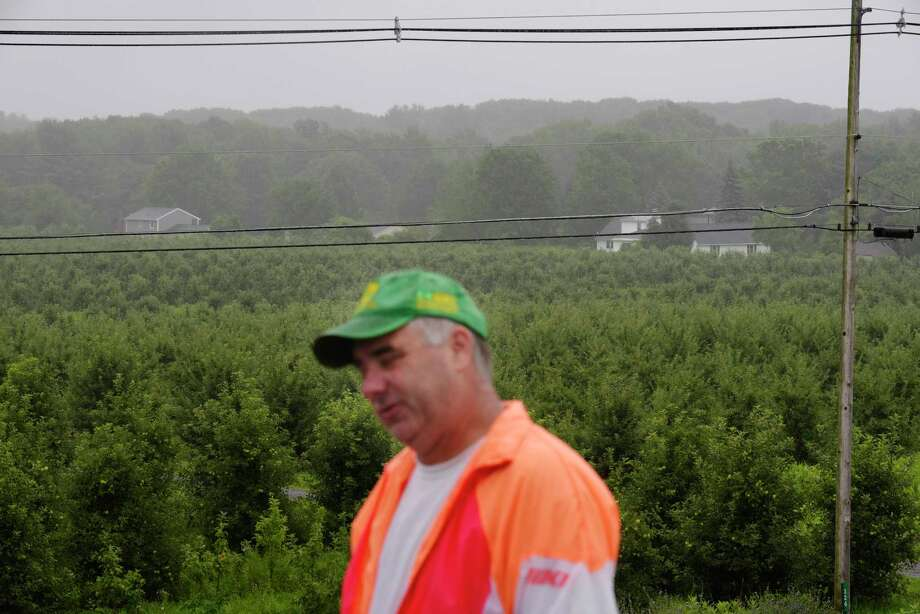 Jeremy Knight, owner of Knight Orchards, stands on the roof of one of his orchard buildings as he looks out over some of his fields and the housing development that is located at the edge of his land on Tuesday, July 25, 2017, in Ballston, N.Y.  Knight says encroaching development is driving deer onto his property that are eating his produce. (Paul Buckowski / Times Union) Photo: PAUL BUCKOWSKI / 20041093A