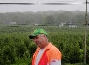 Jeremy Knight, owner of Knight Orchards, stands on the roof of one of his orchard buildings as he looks out over some of his fields and the housing development that is located at the edge of his land on Tuesday, July 25, 2017, in Ballston, N.Y.  Knight says encroaching development is driving deer onto his property that are eating his produce. (Paul Buckowski / Times Union)