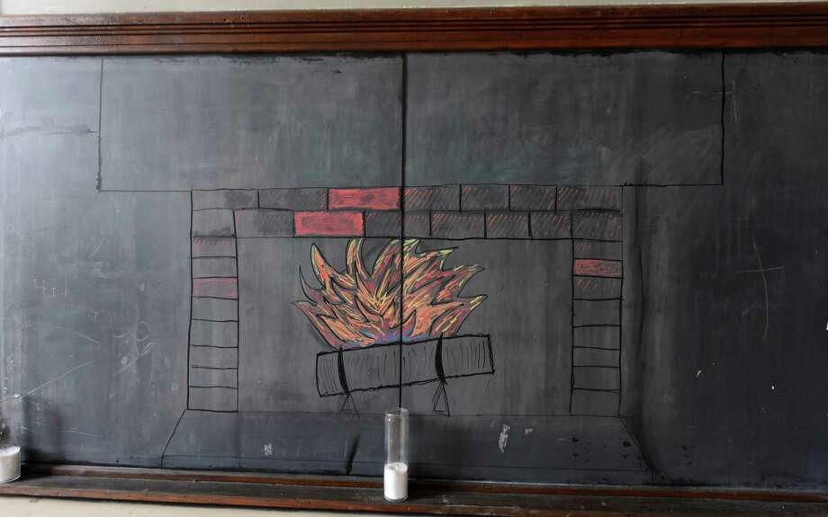 A fireplace is drawn on one of the old chalkboards inside the former Hoosick Falls schoolhouse apartments converted by Jasen VonGuinness on Wednesday, May, 10, 2017, in Hoosick Falls, N.Y. (Will Waldron/Times Union) Photo: Will Waldron / 20040431A