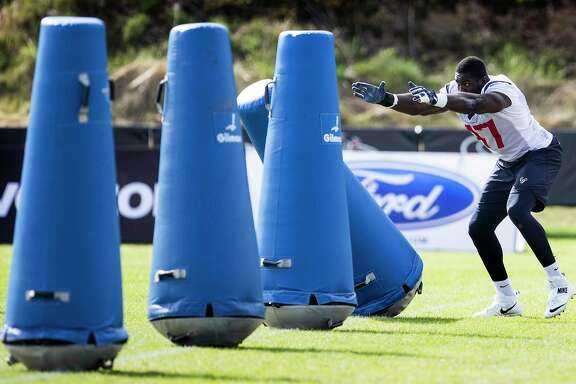 Texans linebacker Eric Lee takes aim at a row of blocking dummies during Saturday's practice session at The Greenbrier in White Sulphur Springs, W.Va.