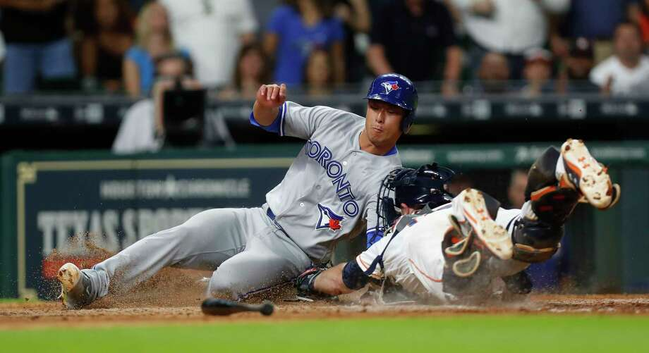 Houston Astros catcher Brian McCann (16) tries to tag Toronto Blue Jays Rob Refsnyder (39) out at home during the tenth inning of an MLB game at Minute Maid Park, Saturday, Aug. 5, 2017, in Houston. Photo: Karen Warren, Houston Chronicle / @ 2017 Houston Chronicle
