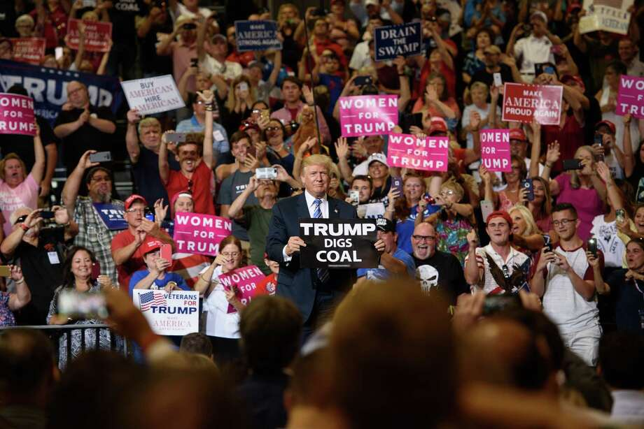 """Donald Trump holds a """"Trump Digs Coal"""" sign during a rally in Huntington, W.Va., last week. Photo: Justin Merriman, Stringer / 2017 Getty Images"""
