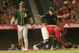 ANAHEIM, CALIFORNIA - AUGUST 05:  Mark Canha #20 of the Oakland Athletics reacts after being safe at home on a double steal as catcher Martin Maldonado #12 of the Los Angeles Angels of Anaheim retrieves the ball in the sixth inning at Angel Stadium of Anaheim on August 5, 2017 in Anaheim, California.  (Photo by Stephen Dunn/Getty Images)