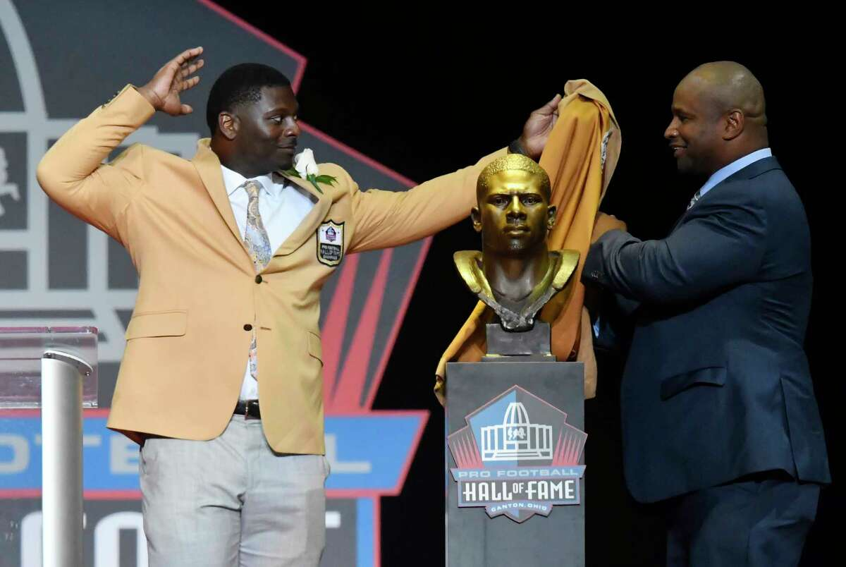 Former NFL player LaDainian Tomlinson, left, and his presenter Lorenzo Neal, unveil his bust before his speech during an induction ceremony at the Pro Football Hall of Fame Saturday, Aug. 5, 2017, in Canton, Ohio. (AP Photo/David Richard)