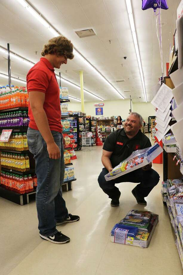 Brookshire Brothers store manager Jeff Fitzgerald shows Greyson Riche how he wants the school supply section stocked. Riche is a senior and plays football for the Dayton Broncos team. Photo: David Taylor