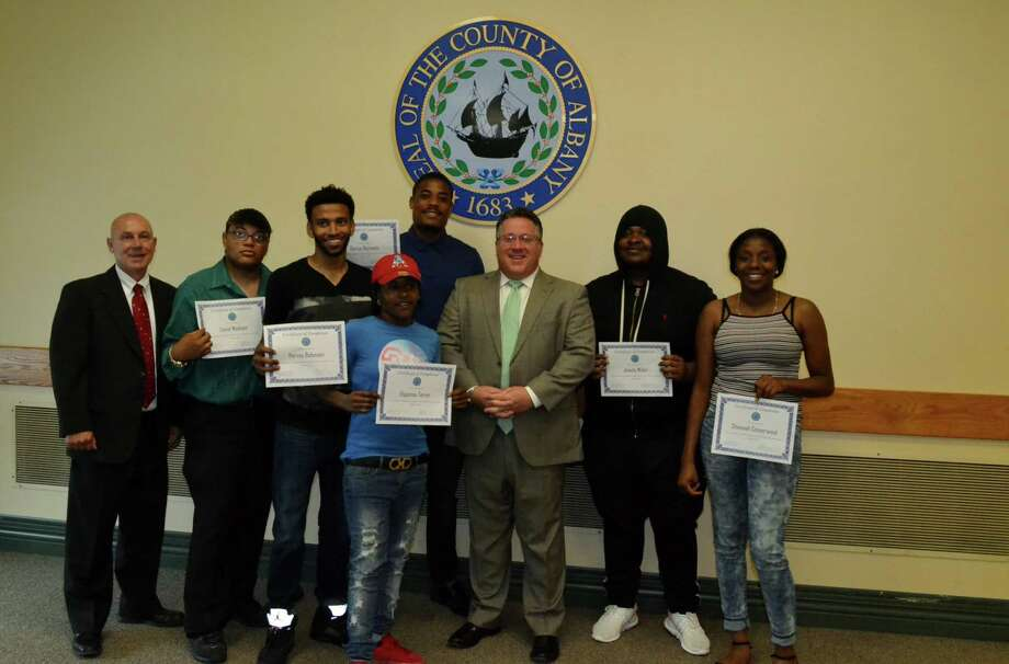 Albany County Executive Dan McCoy, center, hosts the Rite of Passage for six Project Growth graduates in August 2017. Project Growth involves juveniles learning new construction, home remodeling and computer skills so as to make money to give back to victims of low-level crimes they committed. Darrius Burnette, in the blue shirt, is to the left of McCoy. (Provided)