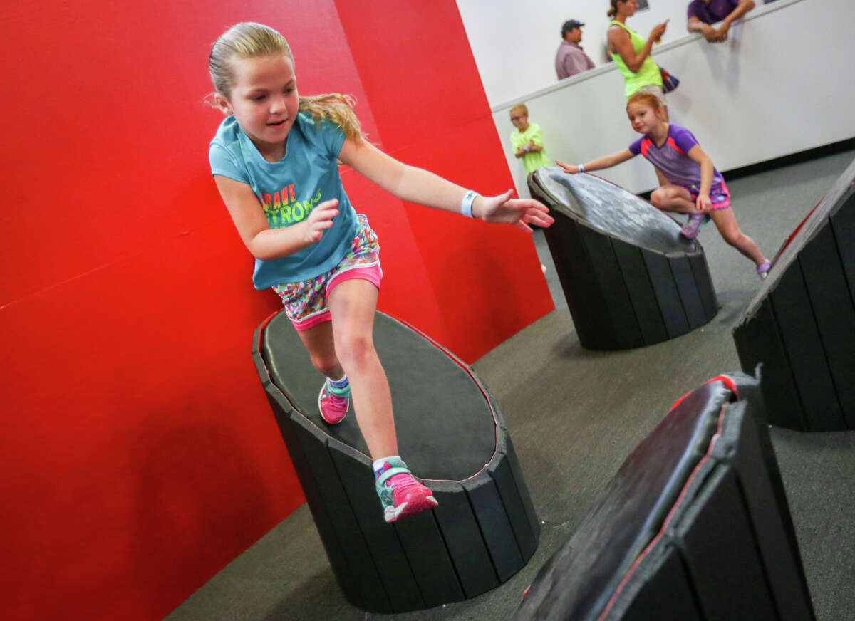 Bayley Trout, 8, leaps from platform to platform during the grand opening of Obstacle Warrior Kids on Saturday, Aug. 5, 2017, in Spring.