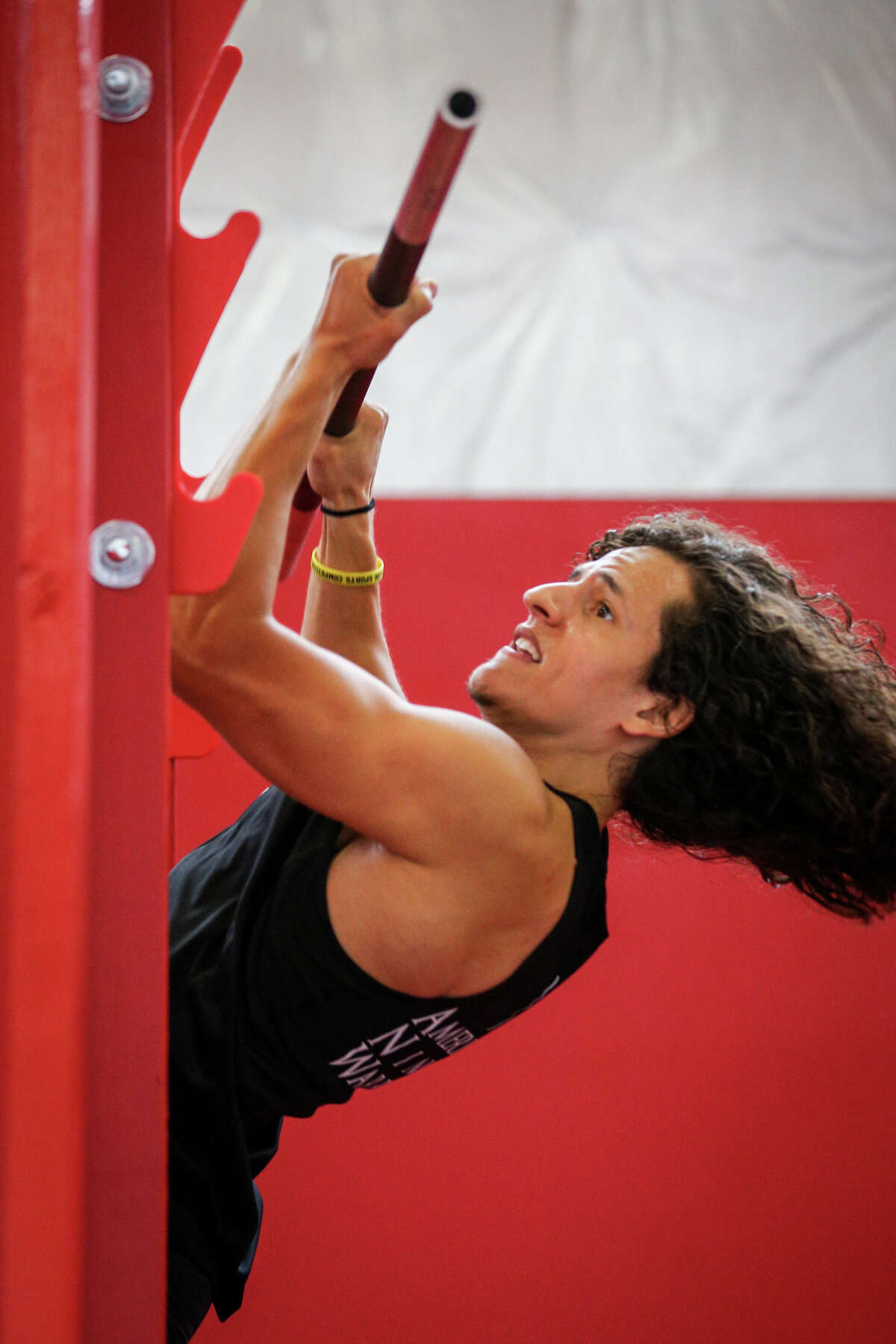 Daniel Gil, a professional Ninja Warrior athlete and two time national finalist on American Ninja Warrior, demonstrates the salmon ladder, an ascending pull up bar system, during the grand opening of Obstacle Warrior Kids on Saturday, Aug. 5, 2017, in Spring.